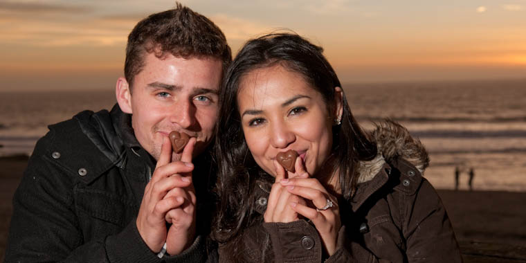 Sendy and Bryan kissing heart-shaped chocolates in Half Moon Bay